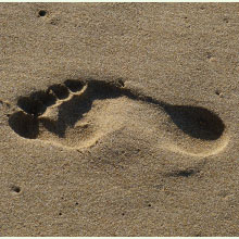 An impression of a foot in the sand